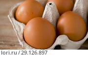Купить «close up of eggs in cardboard box on wooden table», видеоролик № 29126897, снято 21 августа 2018 г. (c) Syda Productions / Фотобанк Лори