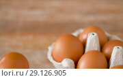 Купить «close up of eggs in cardboard box on wooden table», видеоролик № 29126905, снято 21 августа 2018 г. (c) Syda Productions / Фотобанк Лори