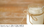 Купить «yogurt or sour cream in glass jar on wooden table», видеоролик № 29126953, снято 21 августа 2018 г. (c) Syda Productions / Фотобанк Лори