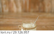 Купить «yogurt or sour cream in glass jar on wooden table», видеоролик № 29126957, снято 21 августа 2018 г. (c) Syda Productions / Фотобанк Лори
