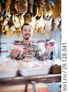 Купить «happy male shop assistant demonstrating sorts of meat in shop», фото № 29128041, снято 2 января 2017 г. (c) Яков Филимонов / Фотобанк Лори