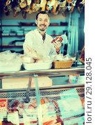 Купить «Seller offering sorts of meat», фото № 29128045, снято 2 января 2017 г. (c) Яков Филимонов / Фотобанк Лори