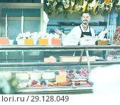 Купить «Seller offering displayed sorts of meat», фото № 29128049, снято 2 января 2017 г. (c) Яков Филимонов / Фотобанк Лори