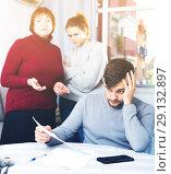 Купить «Frustrated man with papers on background with discontented family», фото № 29132897, снято 27 ноября 2017 г. (c) Яков Филимонов / Фотобанк Лори