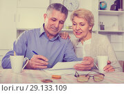 Купить «Mature married couple discuss contract and sign important documents», фото № 29133109, снято 21 марта 2019 г. (c) Яков Филимонов / Фотобанк Лори