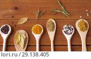 Купить «spoons with different spices on wooden table», видеоролик № 29138405, снято 20 сентября 2018 г. (c) Syda Productions / Фотобанк Лори