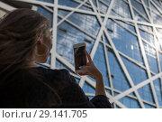 Купить «Girl makes a photo of a stylish building.», фото № 29141705, снято 29 августа 2018 г. (c) Женя Канашкин / Фотобанк Лори