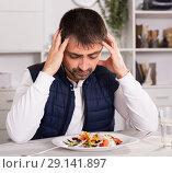 Купить «Portrait of sadly man before eating vegetable salad», фото № 29141897, снято 25 декабря 2017 г. (c) Яков Филимонов / Фотобанк Лори