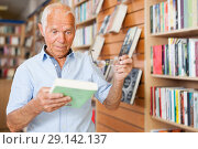 charismatic senior male customer visiting bookshop in search of interesting fiction. Стоковое фото, фотограф Яков Филимонов / Фотобанк Лори