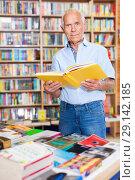 Купить «Focused elderly man looking for information in books in bookstore», фото № 29142185, снято 11 июня 2018 г. (c) Яков Филимонов / Фотобанк Лори