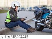 Купить «Девушка сидит на асфальте с телефоном в руках возле мотоцикла», фото № 29142229, снято 15 сентября 2018 г. (c) Кекяляйнен Андрей / Фотобанк Лори