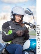 Купить «Девушка мотоциклистка читает сообщение в телефоне, сидя на мотоцикле», фото № 29142241, снято 15 сентября 2018 г. (c) Кекяляйнен Андрей / Фотобанк Лори