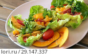 Купить «Colorful salad with baked pumpkin. Recipe: lettuce leaves, pieces of pumpkin, chopped cherry tomatoes and», видеоролик № 29147337, снято 27 августа 2018 г. (c) Яков Филимонов / Фотобанк Лори