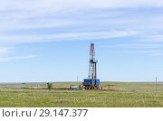Купить «Drilling tower in the steppe. Steppe landscape with drilling rigs and equipment», фото № 29147377, снято 16 июня 2018 г. (c) Вадим Орлов / Фотобанк Лори