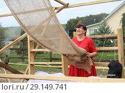 Купить «Продавец делает навес», фото № 29149741, снято 29 сентября 2018 г. (c) Марина Володько / Фотобанк Лори