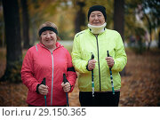 Купить «Two elderly women are standing in a park with sticks for nordic walking. Mid shot», фото № 29150365, снято 30 сентября 2018 г. (c) Константин Шишкин / Фотобанк Лори