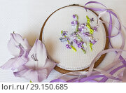 Купить «Close-up view on the embroidery process with satin ribbons of light-violet gladiolus flowers  (These pictures of embroidery and embroidery with satin ribbons were performed by the author of the images)», фото № 29150685, снято 24 сентября 2018 г. (c) Виктория Катьянова / Фотобанк Лори