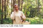 Купить «woman with mushrooms calling on cellphone in woods», видеоролик № 29150729, снято 24 сентября 2018 г. (c) Syda Productions / Фотобанк Лори