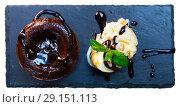 Купить «Sweet lava cake served with vanilla ice cream and mint at black plate», фото № 29151113, снято 23 октября 2019 г. (c) Яков Филимонов / Фотобанк Лори