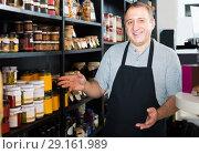 Купить «salesman working in delicatessen section of ordinary grocery», фото № 29161989, снято 5 октября 2016 г. (c) Яков Филимонов / Фотобанк Лори