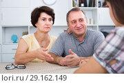 Купить «Worried mature couple listening to young woman», фото № 29162149, снято 21 октября 2018 г. (c) Яков Филимонов / Фотобанк Лори