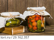 Купить «Food. Homemade canned vegetables in jars. Marinated tomatoes and cucumbers on the background of a wooden table in a rural style», фото № 29162357, снято 9 сентября 2018 г. (c) Светлана Евграфова / Фотобанк Лори