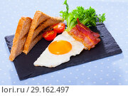 Купить «Cooked eggs with bacon, toasted bread, tomatoes and lettuce at plate on table», фото № 29162497, снято 25 апреля 2019 г. (c) Яков Филимонов / Фотобанк Лори