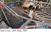 Купить «Coron, Philippines - January 5, 2018: The way of life of children and families in the Filipino slums. Poverty. Children on unsafe wooden bridges from planks on high water. Philippines.», видеоролик № 29162781, снято 5 января 2018 г. (c) Mikhail Davidovich / Фотобанк Лори