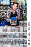 Купить «Man standing near the counter and selling details for plumbing in hardware shop», фото № 29165501, снято 4 мая 2017 г. (c) Яков Филимонов / Фотобанк Лори