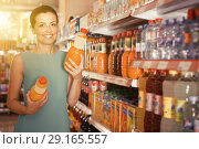 Купить «Portrait of happy woman in the shop choosing juice», фото № 29165557, снято 6 июня 2017 г. (c) Яков Филимонов / Фотобанк Лори
