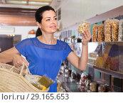 Купить «female customer choosing natural dried berries sold by weight in eco market», фото № 29165653, снято 13 июня 2017 г. (c) Яков Филимонов / Фотобанк Лори