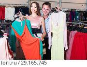 Купить «Young woman and man looking for new dress in showroom», фото № 29165745, снято 11 апреля 2017 г. (c) Яков Филимонов / Фотобанк Лори
