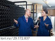 Купить «Adult winery workers holding bottle of wine», фото № 29172837, снято 20 октября 2018 г. (c) Яков Филимонов / Фотобанк Лори