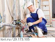 Купить «Experienced electrician laying electric wires in building under construction», фото № 29173105, снято 28 мая 2018 г. (c) Яков Филимонов / Фотобанк Лори