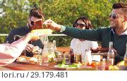 Купить «happy friends eating and drinking at rooftop party», видеоролик № 29179481, снято 26 сентября 2018 г. (c) Syda Productions / Фотобанк Лори