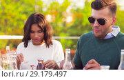 Купить «happy friends eating at rooftop party», видеоролик № 29179497, снято 26 сентября 2018 г. (c) Syda Productions / Фотобанк Лори