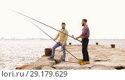 Купить «happy friends with fishing rods on pier», видеоролик № 29179629, снято 28 сентября 2018 г. (c) Syda Productions / Фотобанк Лори