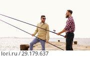 Купить «happy friends with fishing rods on pier», видеоролик № 29179637, снято 28 сентября 2018 г. (c) Syda Productions / Фотобанк Лори