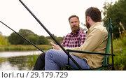 Купить «friends with smartphone and beer fishing on lake», видеоролик № 29179729, снято 28 сентября 2018 г. (c) Syda Productions / Фотобанк Лори
