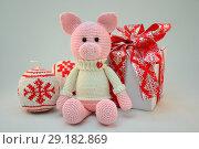Розовый игрушечный поросенок в свитере сидит рядом с подарочной коробкой с красным бантом. Стоковое фото, фотограф Иванна Кошка / Фотобанк Лори
