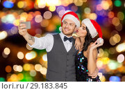 Купить «couple in santa hats taking selfie at christmas», фото № 29183845, снято 15 декабря 2017 г. (c) Syda Productions / Фотобанк Лори