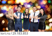 happy friends in party clothes showing thumbs up. Стоковое фото, фотограф Syda Productions / Фотобанк Лори