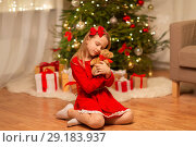 Купить «girl in red dress hugging teddy bear at home», фото № 29183937, снято 22 декабря 2017 г. (c) Syda Productions / Фотобанк Лори