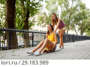 Купить «teenage girls riding skateboard on city street», фото № 29183989, снято 19 июля 2018 г. (c) Syda Productions / Фотобанк Лори