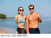 Купить «couple of athletes showing thumbs up on beach», фото № 29184001, снято 1 августа 2018 г. (c) Syda Productions / Фотобанк Лори