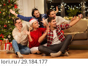 Купить «friends celebrating christmas and taking selfie», фото № 29184177, снято 17 декабря 2017 г. (c) Syda Productions / Фотобанк Лори