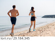 Купить «couple in sports clothes running along on beach», фото № 29184345, снято 1 августа 2018 г. (c) Syda Productions / Фотобанк Лори