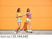 Купить «teenage girls riding skateboard on city street», фото № 29184645, снято 19 июля 2018 г. (c) Syda Productions / Фотобанк Лори