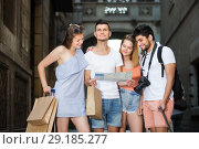 Купить «Portrait of smiling tourists with map and baggage in European city», фото № 29185277, снято 22 июня 2017 г. (c) Яков Филимонов / Фотобанк Лори
