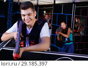 Купить «Portrait of excited guy with laser pistol playing laser tag in arena», фото № 29185397, снято 27 августа 2018 г. (c) Яков Филимонов / Фотобанк Лори